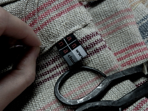 hand-sewn edging on hand-woven fabric